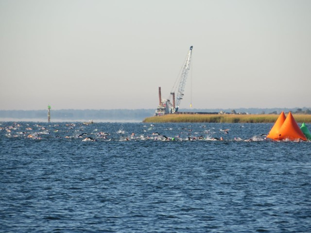 A mass of swimmers passing the buoy that marks the turn point