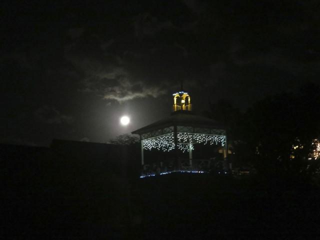 The full moon shines behind this gazebo