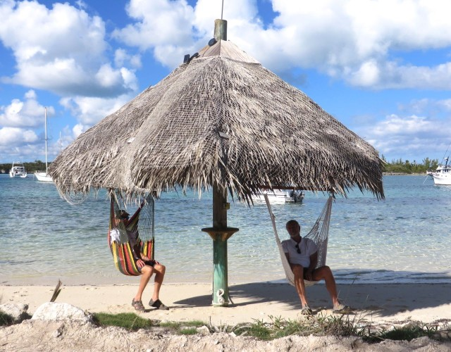 The guys are hanging out in  swinging chair hammocks under a tiki style roof.