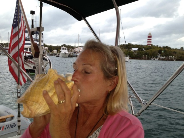 Michele finally blows that conch horn at sunset, with the Elbow Reef Lighthouse in the background.