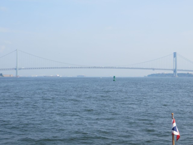The Verranzano Narrows Bridge ahead appears in the distant haze.