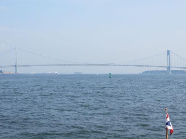 The Verranzano Narrows Bridge ahead appears in the distant haze.