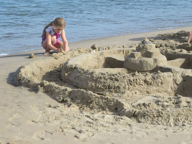 A little girl working on her sand fort.