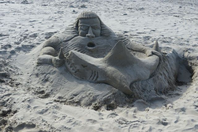 A very creative man built this sand sculpture. His description of it? Neptune is protecting his beer from the shark!