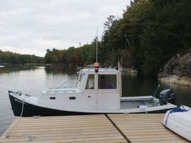 The lobster boat with its buoy colors displayed on the cabin top.