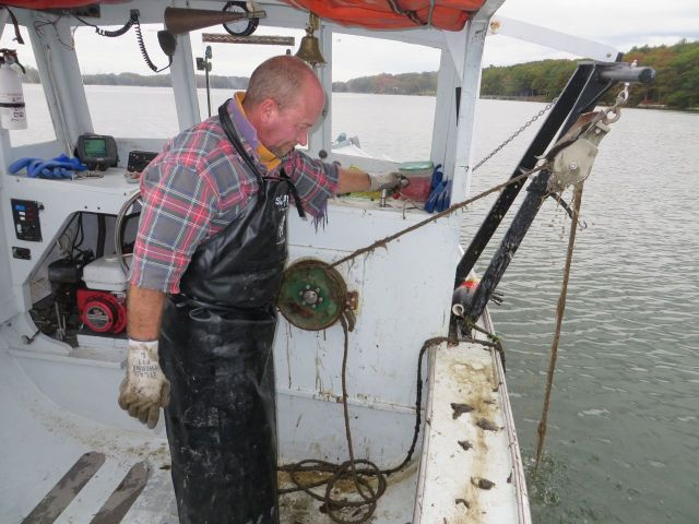 He attaches the line to the wheel that hauls the lobster crate up and out of the water.