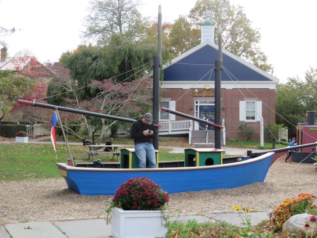 Tim takes a moment to text while standing in the model sailboat.