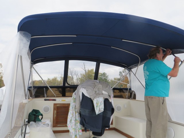 Tempting the bimini with large sheets of plastic to make a the pattern. Very precise work, or at least it should be!