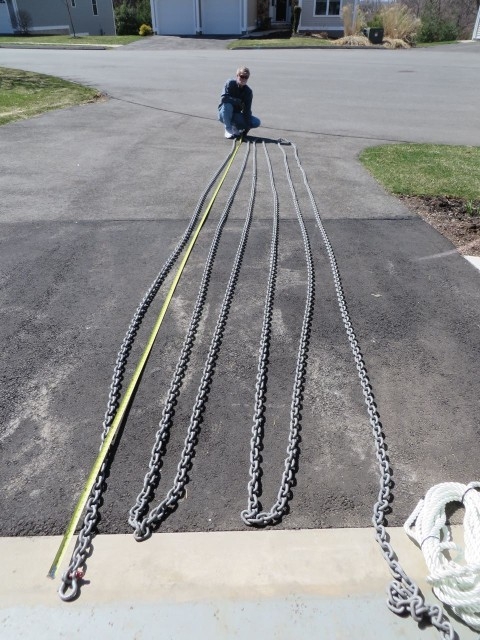 Stretching the chain out in the driveway to measure and mark it in 25 foot intervals.