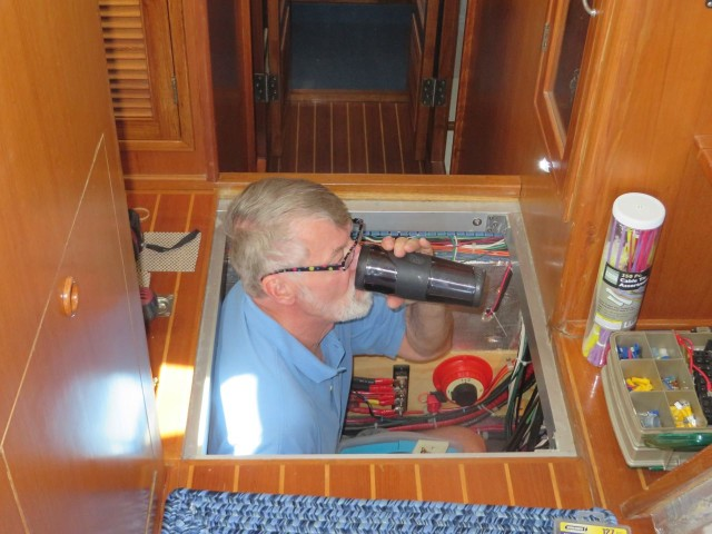 The Captain having his morning coffee while checking on the boat's systems.
