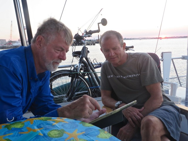 The Captains confer over tomorrow's routes and timing for theatric up the Delaware Bay and River to Chesapeake City (for us.)