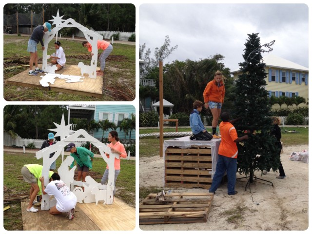 The wooden white nativity scene is assembled and the Christmas tree on top of the large crate so that it stands tall.