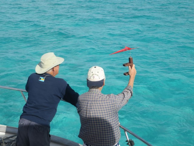 David and John are checking the wind in order to place the start line and the windward mark.