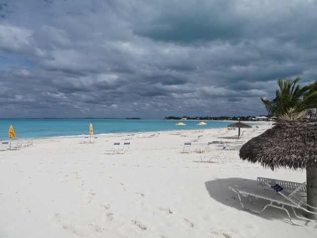 First look at Treasure Beach, a long crescent shaped beach of fine grain beautiful sand. So civilized there are umbrellas, but you have to pay $10 to sit under one.
