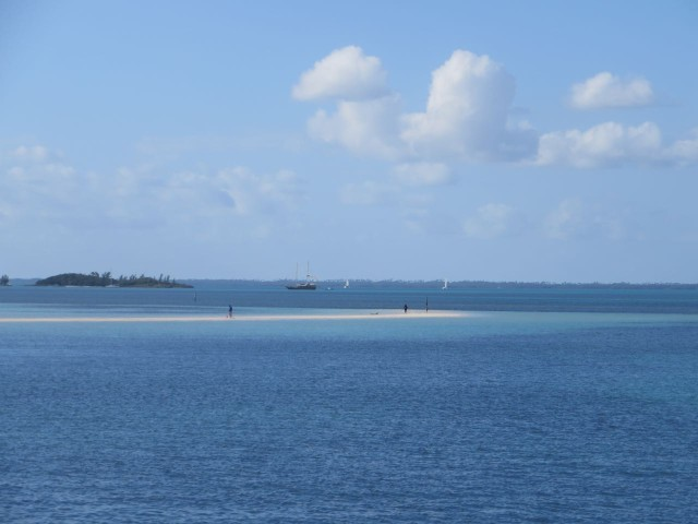 In the distance, over the sandbar beach, is a two-masted schooner.