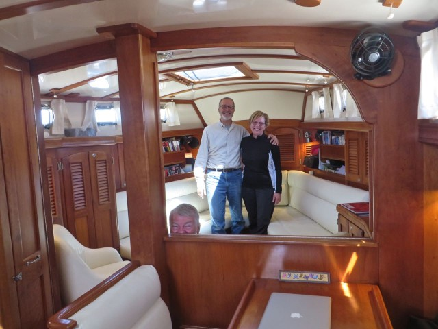 Cheryl And Dudley are standing in what is both salon area and the master cabin. A couple of easy slides and pulls and a queen size berth appears. Yes, that is Al photo-bombing the photo.