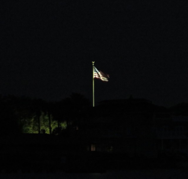 The illuminated United States flag on shore glowed in the early morning.