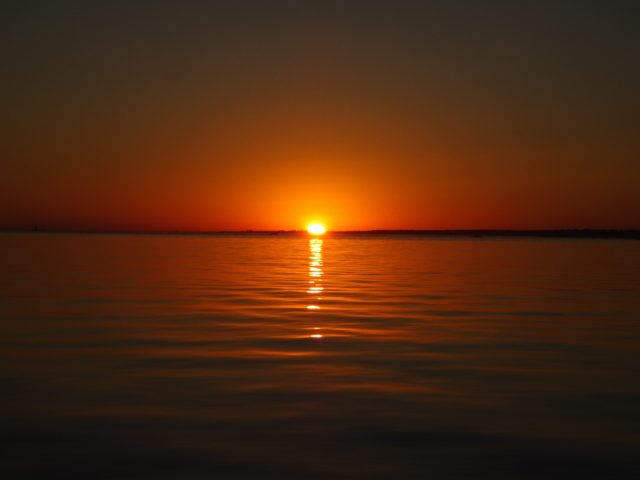 A bright yellow sun in a deep red-orange sky says good night to us.