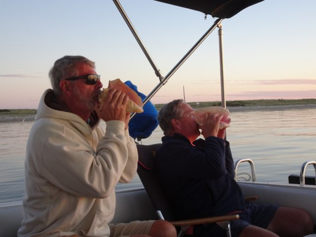 Al and Dean blow their conch horns for the sun's beautiful performance.